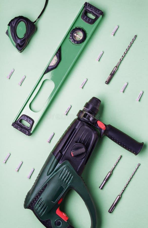 Επίπεδο σχεδιάγραμμα: perforator και άλλα εργαλεία χεριών για την κατασκευή και την επισκευή σε ένα πράσινο υπόβαθρο στοκ φωτογραφία