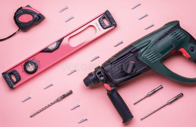 Επίπεδο σχεδιάγραμμα: perforator και άλλα εργαλεία χεριών για την κατασκευή και την επισκευή σε ένα ρόδινο υπόβαθρο στοκ φωτογραφίες με δικαίωμα ελεύθερης χρήσης