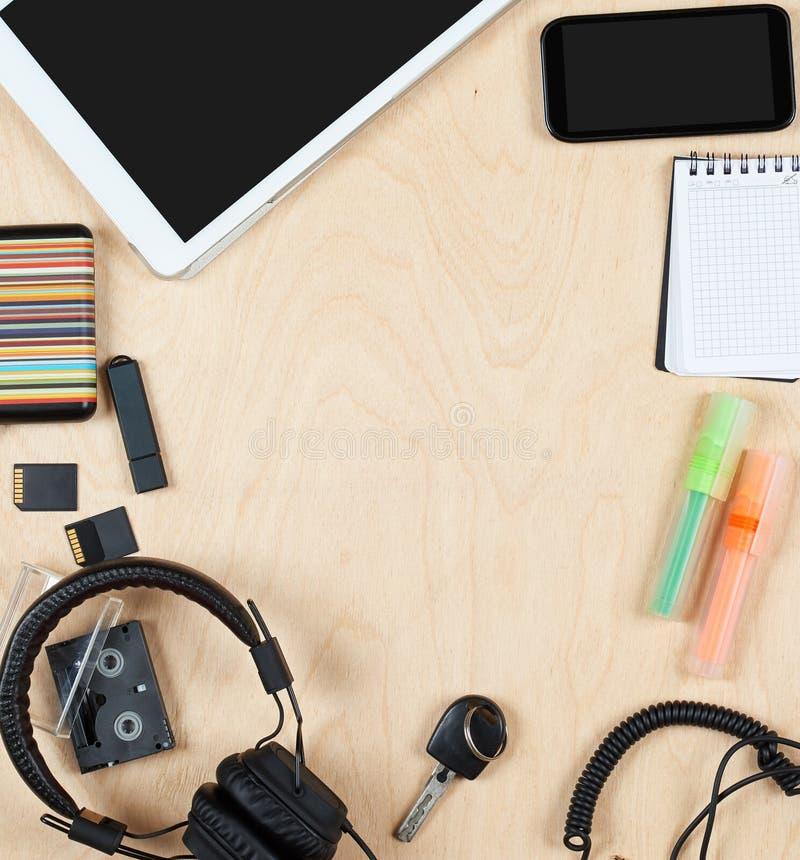 Επίπεδος βάλτε τα εργαλεία και τις προμήθειες γραφείων, τον υπολογιστή ταμπλετών, τις ακουστικές κάρτες ακουστικών και άλλη ουσία στοκ φωτογραφία