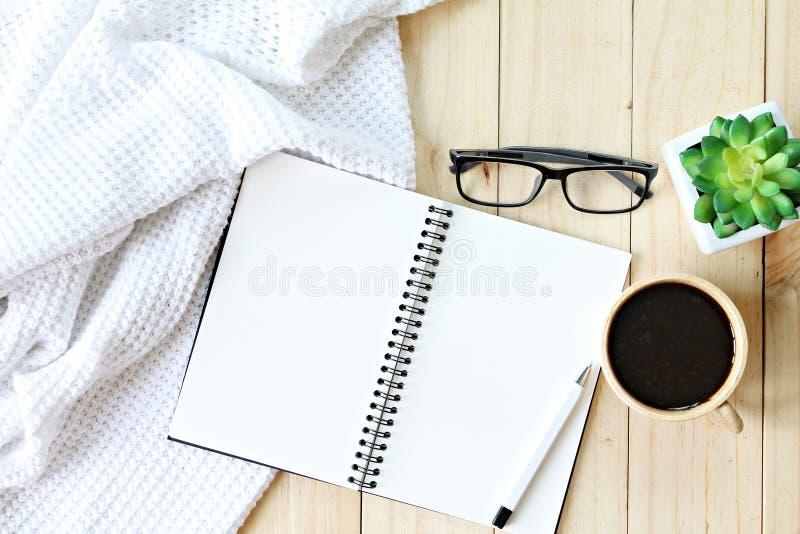 Επίπεδος βάλτε του άσπρου πλεκτού καλύμματος, του φλιτζανιού του καφέ και του κενού εγγράφου σημειωματάριων για το ξύλινο υπόβαθρ στοκ φωτογραφία