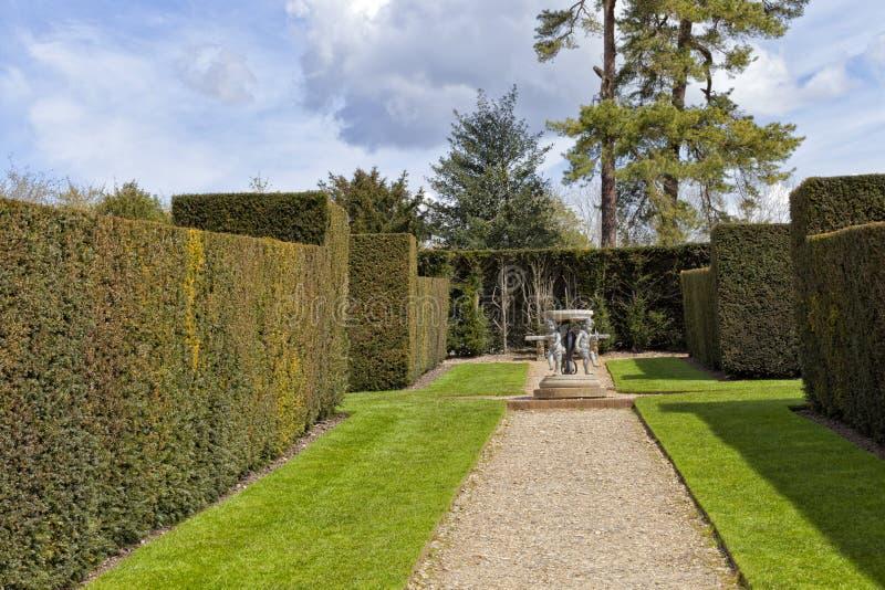 Επίσημος κήπος με τη διακόσμηση ηλιακών ρολογιών στο κέντρο μεταξύ των τοίχων φρακτών στοκ εικόνες