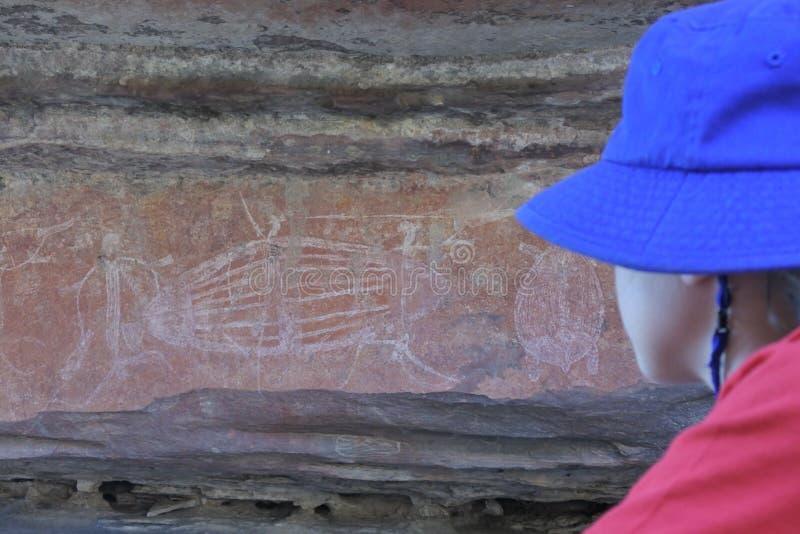 Επίσκεψη τουριστών κοριτσιών επί του τόπου τέχνης βράχου Ubirr στην εθνική Βόρεια Περιοχή πάρκων Kakadu της Αυστραλίας στοκ φωτογραφία