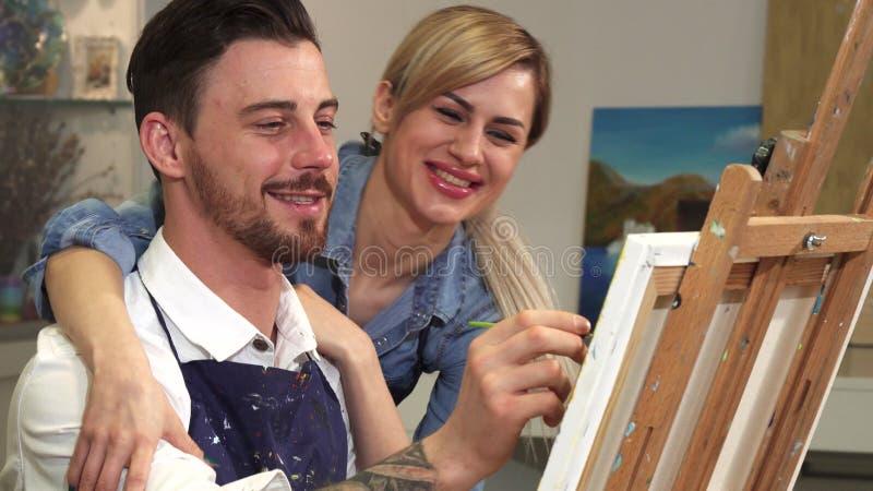 Επαγγελματίας καλλιτέχνης που χρωματίζει στον καμβά τη φίλη του που αγκαλιάζει τον στοκ εικόνες με δικαίωμα ελεύθερης χρήσης