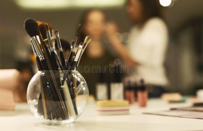 Επαγγελματικές βούρτσες Makeup στο γυαλί που στέκεται στον πίνακα του καλλιτέχνη στοκ φωτογραφίες