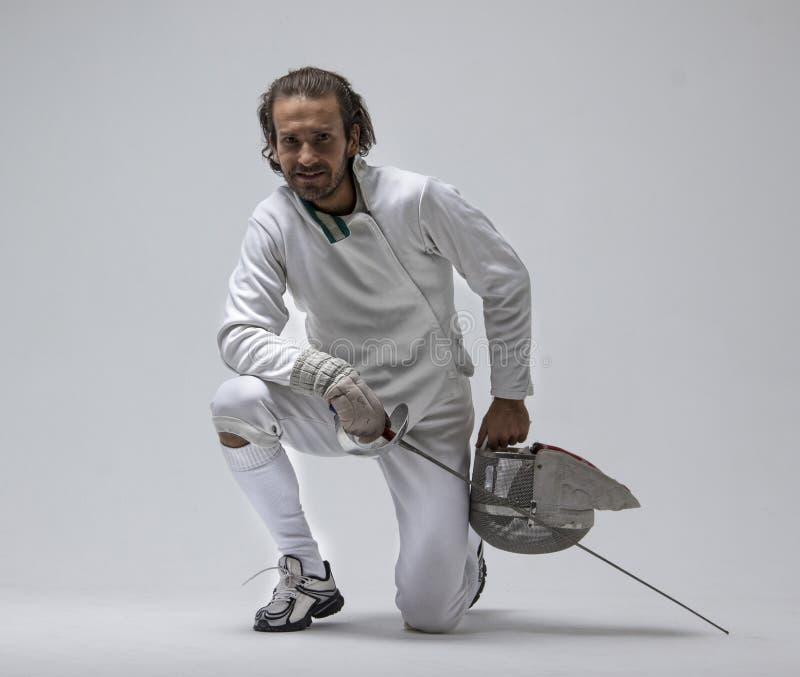 Επαγγελματική αρσενική εύθυμη μάσκα εκμετάλλευσης ξιφομάχων και sabre μένοντας στο γόνατό του στοκ φωτογραφίες