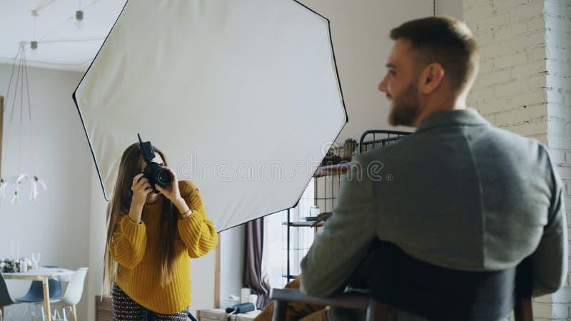 Επαγγελματική γυναίκα φωτογράφων που παίρνει τη φωτογραφία του πρότυπου κοριτσιού επιχειρηματιών με τη ψηφιακή κάμερα στο στούντι στοκ εικόνες με δικαίωμα ελεύθερης χρήσης