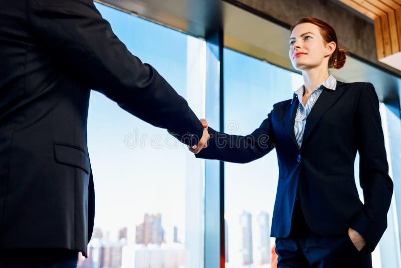 Επαγγελματικοί επιχειρησιακοί γυναίκα και άνδρας στα επίσημα χέρια τινάγματος κοστουμιών στο εσωτερικό στοκ εικόνες