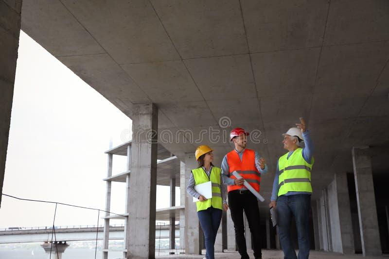 Επαγγελματικοί μηχανικοί στον εξοπλισμό ασφάλειας στο εργοτάξιο οικοδομής στοκ φωτογραφία με δικαίωμα ελεύθερης χρήσης