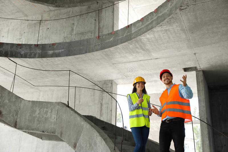 Επαγγελματικοί μηχανικοί στον εξοπλισμό ασφάλειας στο εργοτάξιο οικοδομής στοκ εικόνα με δικαίωμα ελεύθερης χρήσης