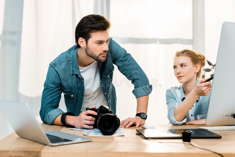 επαγγελματικοί νέοι φωτογράφοι που χρησιμοποιούν τους υπολογιστές γραφείου και στοκ φωτογραφίες με δικαίωμα ελεύθερης χρήσης
