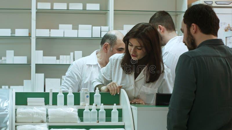 Επαγγελματικοί φαρμακοποιός και τεχνικός φαρμακείων που εργάζονται στο φαρμακείο στοκ φωτογραφία