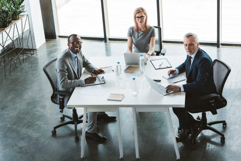 επαγγελματικοί multiethnic επιχειρηματίες που χαμογελούν στη κάμερα καθμένος από κοινού στοκ φωτογραφία