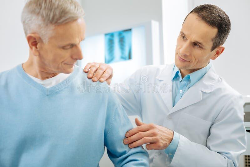 Επαγγελματικός έξυπνος γιατρός που συνεργάζεται με έναν ασθενή στοκ φωτογραφία