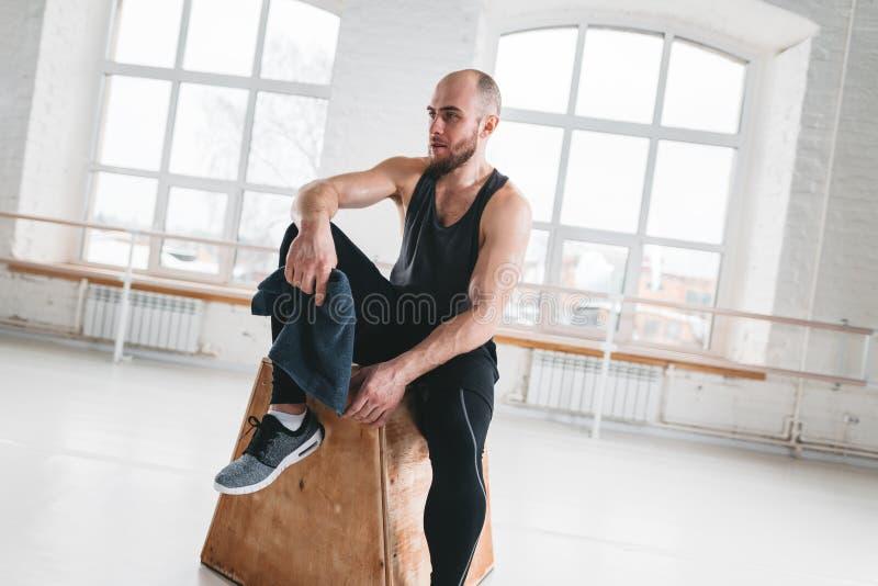 Επαγγελματικός αθλητής workout που στηρίζεται μετά από τη διαγώνια σύνοδο εργασίας στη γυμναστική ικανότητας στοκ εικόνες