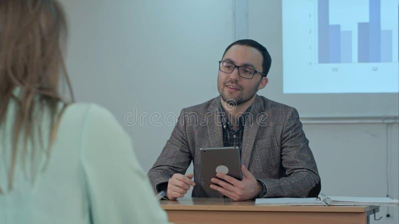 Επαγγελματικός αρσενικός δάσκαλος που εξηγεί τις κύριες ιδέες του δοκίμιου που κάνουν τη συζήτηση μεταξύ των σπουδαστών που υποβά στοκ εικόνες με δικαίωμα ελεύθερης χρήσης