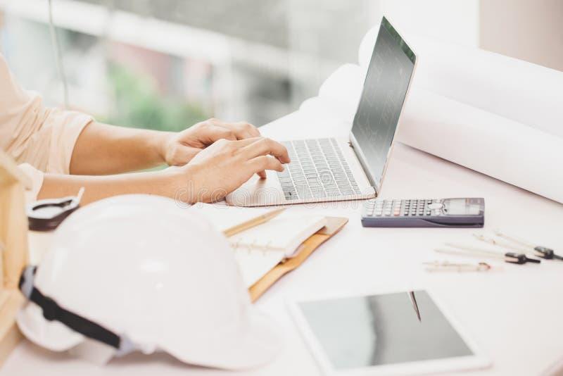 Επαγγελματικός εγχώριος σχεδιαστής μηχανικών αρχιτεκτονικής που εργάζεται με το φορητό προσωπικό υπολογιστή στο γραφείο στοκ εικόνα με δικαίωμα ελεύθερης χρήσης