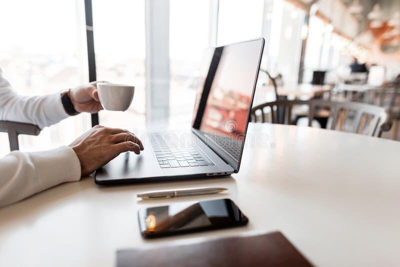 Επαγγελματικός επιτυχής επιχειρηματίας που εργάζεται σε ένα lap-top και ένα καυτό americano κατανάλωσης σε ένα φωτεινό γραφείο στοκ εικόνα
