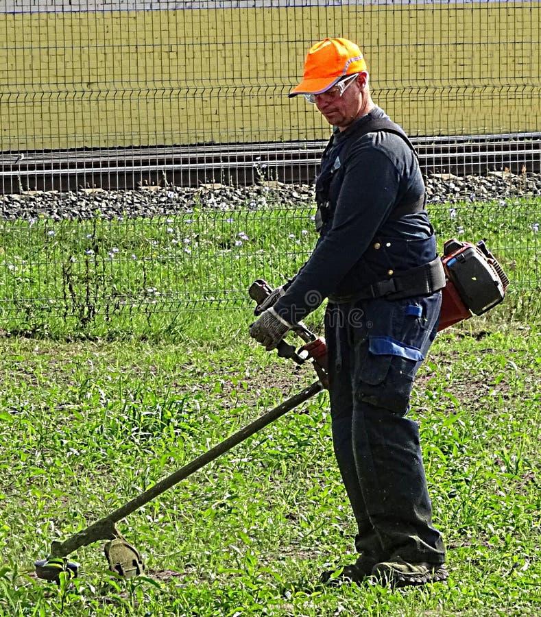 Επαγγελματικός εργαζόμενος ατόμων κοπτών χλόης στον τομέα πόλεων στοκ φωτογραφία με δικαίωμα ελεύθερης χρήσης