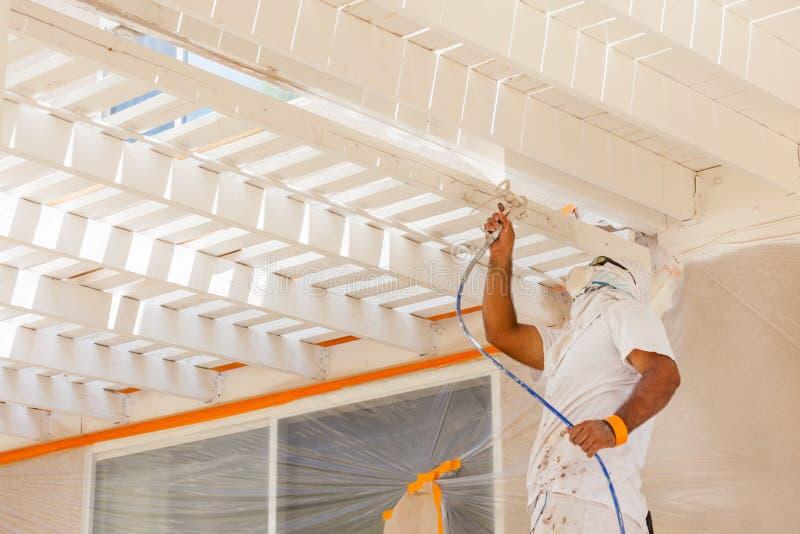 Επαγγελματικός ζωγράφος σπιτιών που φορά το του προσώπου χρώμα ψεκασμού προστασίας στοκ εικόνα