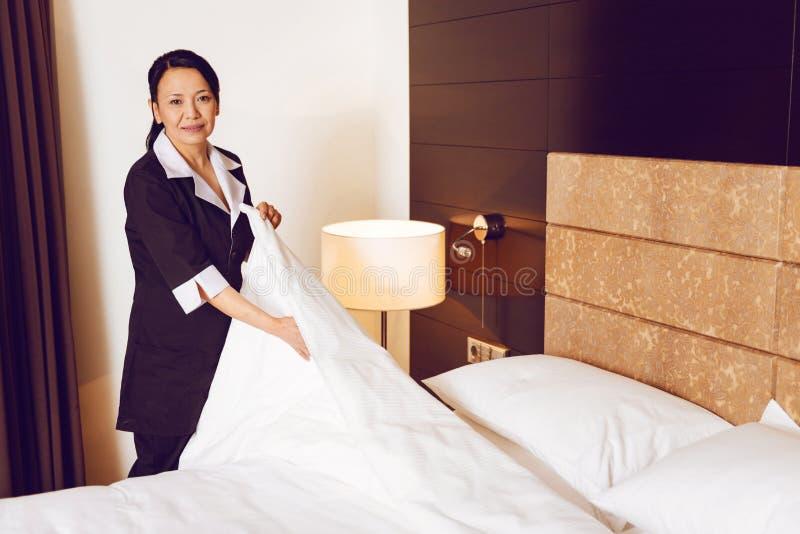 Επαγγελματικός καθαριστής δωματίων που κάνει το κρεβάτι στοκ εικόνες