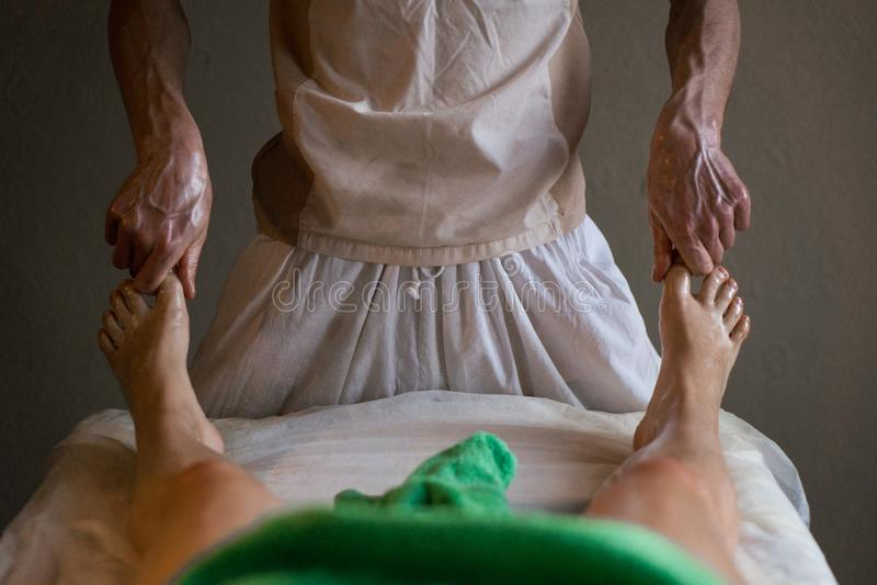 Επαγγελματικός μασέρ που κάνει το βαθύ λαδωμένο ιστός μασάζ σε ένα κορίτσι στη σύνοδο μασάζ Ayurveda στοκ εικόνα με δικαίωμα ελεύθερης χρήσης