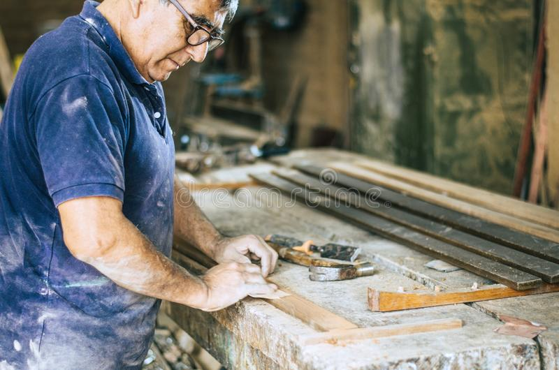 Επαγγελματικός ξυλουργός που στρώνει με άμμο και που την ξύλινη επιφάνεια στοκ φωτογραφία με δικαίωμα ελεύθερης χρήσης