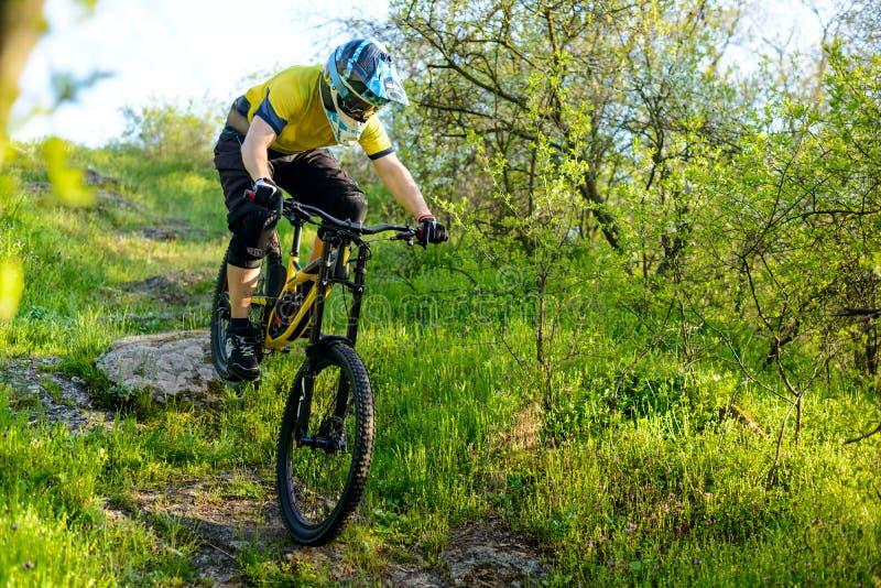 Επαγγελματικός ποδηλάτης στο κίτρινο οδηγώντας ποδήλατο μπλουζών και κρανών κάτω από το δύσκολο Hill Ακραία αθλητική έννοια στοκ εικόνες