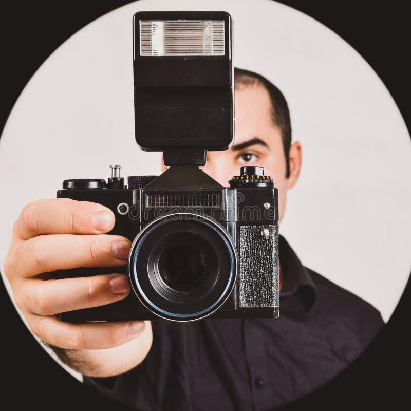 Επαγγελματικός φωτογράφος που κρατά την παλαιά, αναδρομικά κάμερα ταινιών και το fla στοκ εικόνες