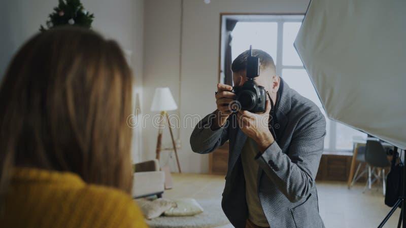 Επαγγελματικός φωτογράφος που παίρνει τις φωτογραφίες του προτύπου στη ψηφιακή κάμερα που λειτουργεί στο στούντιο φωτογραφιών στοκ εικόνα με δικαίωμα ελεύθερης χρήσης