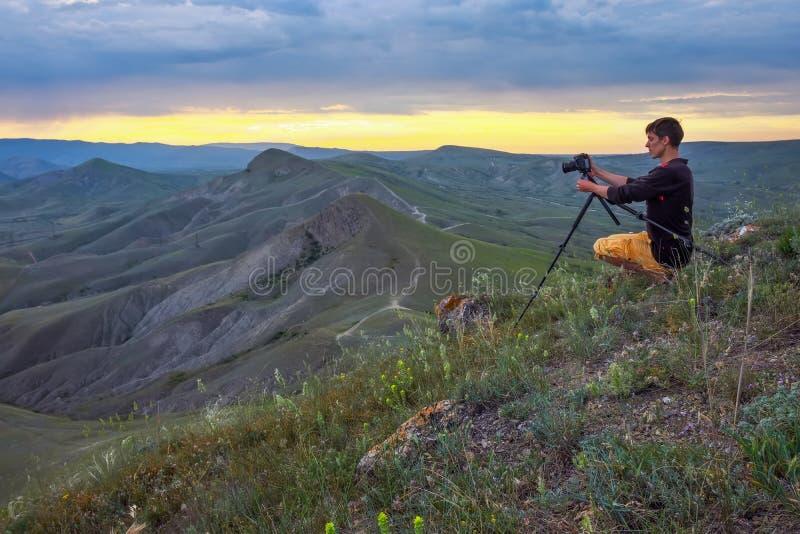 Επαγγελματικός φωτογράφος που χρησιμοποιεί ένα τρίποδο, που παίρνει μια φωτογραφία ενός τοπίου βουνών στοκ εικόνες