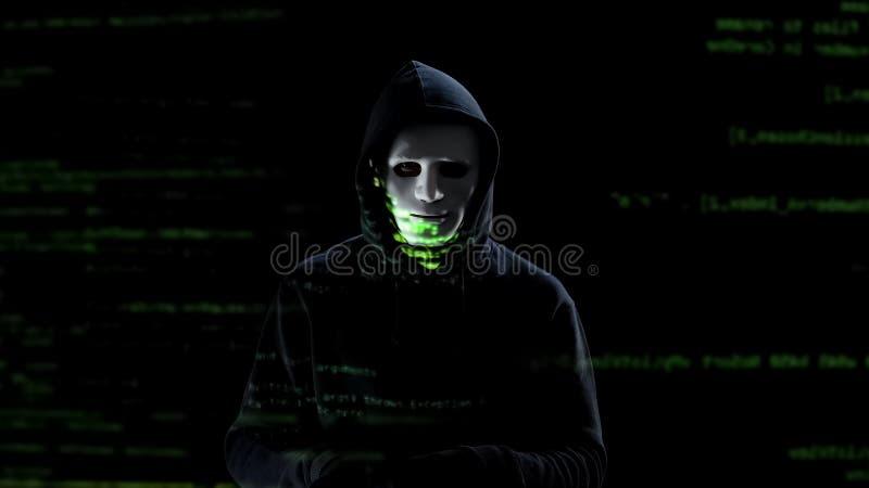 Επαγγελματικός χάκερ στην άσπρη μάσκα που κλέβει τα προσωπικά στοιχεία από το PC, απειλή στοκ φωτογραφία με δικαίωμα ελεύθερης χρήσης