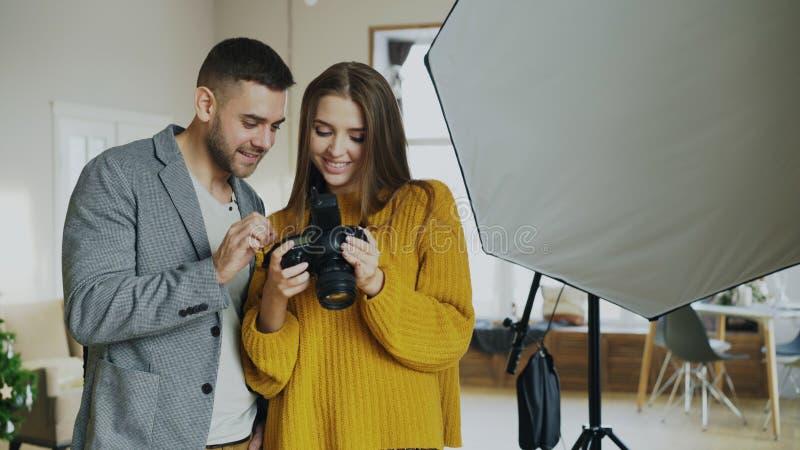Επαγγελματικό άτομο φωτογράφων που παρουσιάζει φωτογραφίες στη ψηφιακή κάμερα στο όμορφο πρότυπο κορίτσι στο στούντιο φωτογραφιών στοκ φωτογραφία με δικαίωμα ελεύθερης χρήσης