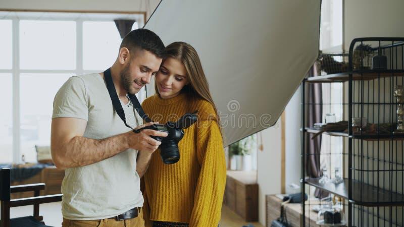 Επαγγελματικό άτομο φωτογράφων που παρουσιάζει φωτογραφίες στη ψηφιακή κάμερα στο όμορφο πρότυπο κορίτσι στο στούντιο φωτογραφιών στοκ φωτογραφίες
