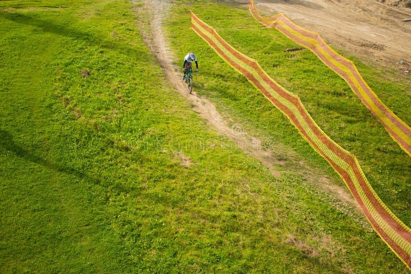 Επαγγελματικό οδηγώντας ποδήλατο ποδηλατών στο ίχνος βουνών ανοίξεων στοκ φωτογραφίες