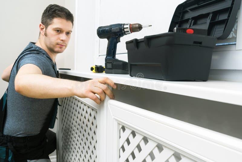 Επαγγελματικό handyman συγκεντρώνοντας γραφείο θερμαντικών σωμάτων στοκ φωτογραφία