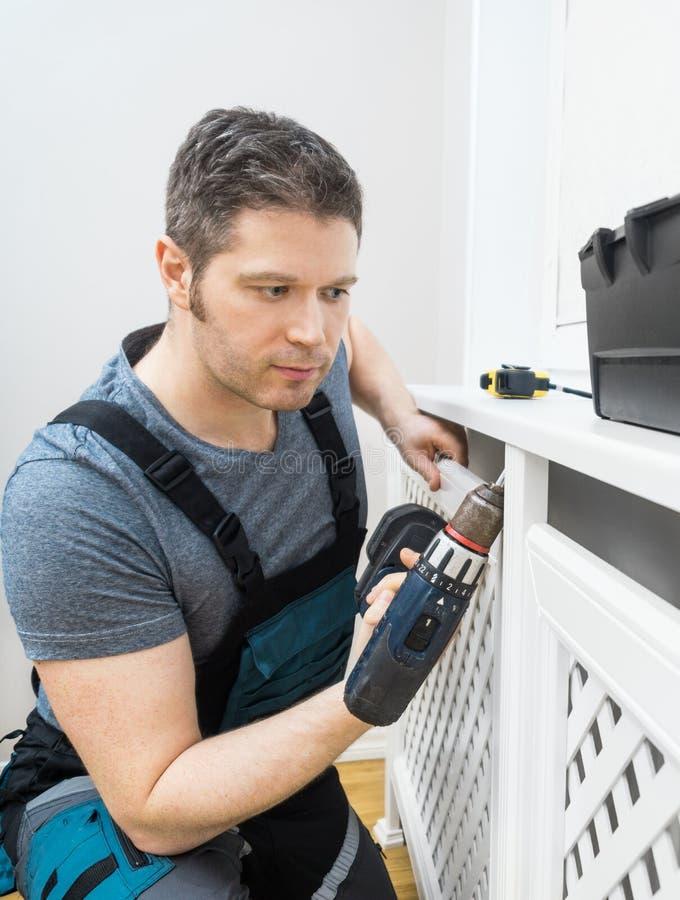 Επαγγελματικό handyman συγκεντρώνοντας γραφείο θερμαντικών σωμάτων στοκ φωτογραφίες
