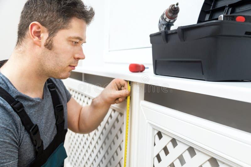 Επαγγελματικό handyman συγκεντρώνοντας γραφείο θερμαντικών σωμάτων στοκ εικόνα με δικαίωμα ελεύθερης χρήσης