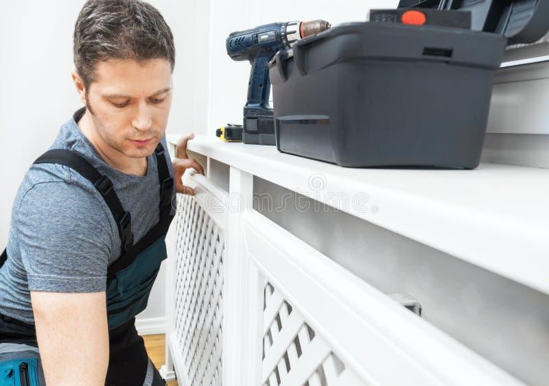 Επαγγελματικό handyman συγκεντρώνοντας γραφείο θερμαντικών σωμάτων στοκ εικόνα