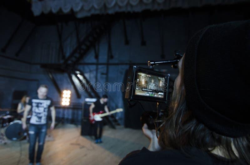 Επαγγελματικό videographer που χρησιμοποιεί τα ψηφιακά βιντεοκάμερα κινηματογράφων για τη μαγνητοσκόπηση ένα μουσικό βίντεο στοκ εικόνα με δικαίωμα ελεύθερης χρήσης