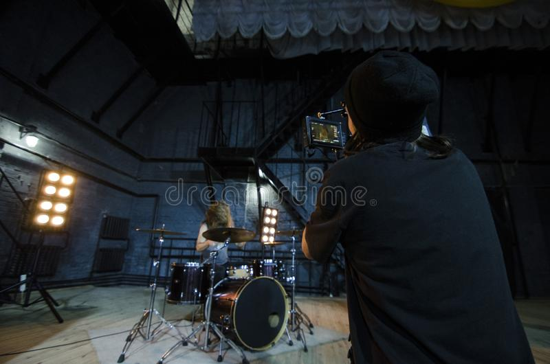 Επαγγελματικό videographer που χρησιμοποιεί τα ψηφιακά βιντεοκάμερα κινηματογράφων για τη μαγνητοσκόπηση ένας τυμπανιστής για ένα στοκ φωτογραφίες