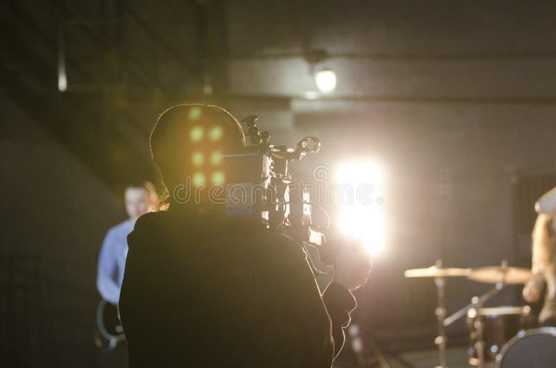 Επαγγελματικό videographer που χρησιμοποιεί τα ψηφιακά βιντεοκάμερα κινηματογράφων για τη μαγνητοσκόπηση ένα μουσικό βίντεο στοκ φωτογραφία με δικαίωμα ελεύθερης χρήσης