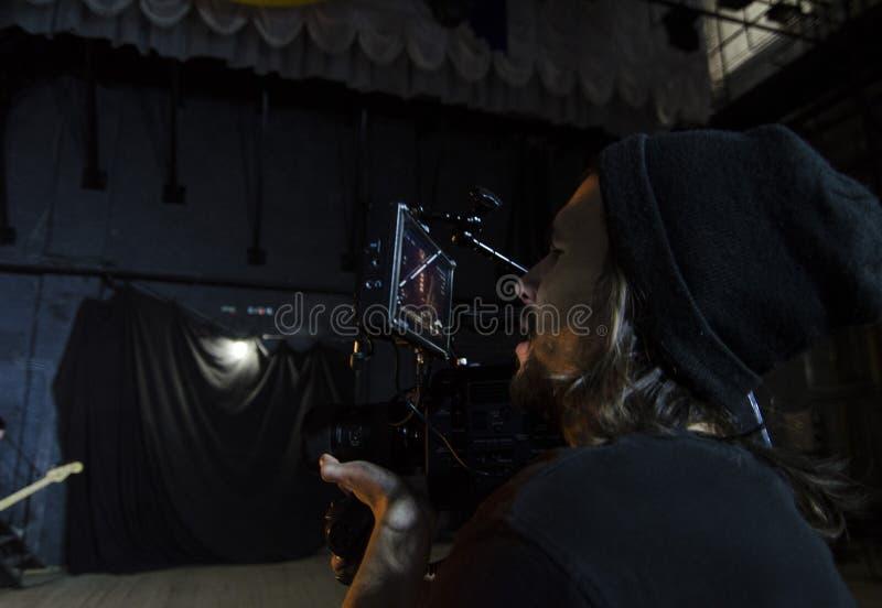 Επαγγελματικό videographer που χρησιμοποιεί τα ψηφιακά βιντεοκάμερα κινηματογράφων για τη μαγνητοσκόπηση ένα μουσικό βίντεο στοκ φωτογραφία