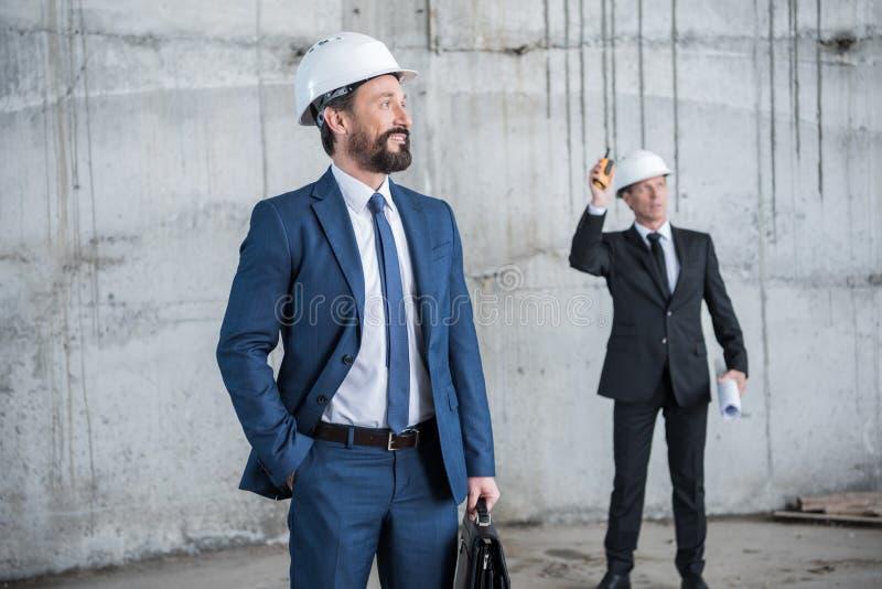 Επαγγελματικοί αρχιτέκτονες στα κράνη που συζητούν το πρόγραμμα στο εργοτάξιο οικοδομής στοκ φωτογραφία