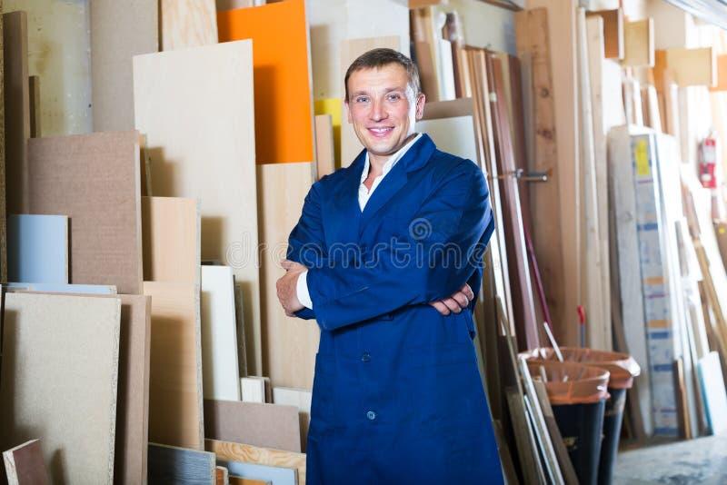 Επαγγελματικός εργάτης που στέκεται με τα κομμάτια κοντραπλακέ στοκ φωτογραφία