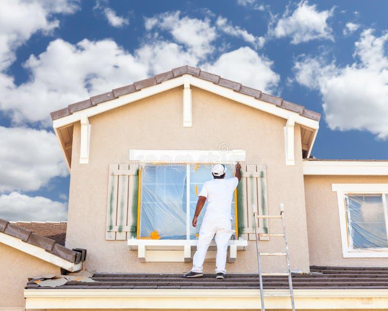 Επαγγελματικός ζωγράφος σπιτιών που χρωματίζει την περιποίηση και τα παραθυρόφυλλα του Α Χ στοκ εικόνα με δικαίωμα ελεύθερης χρήσης