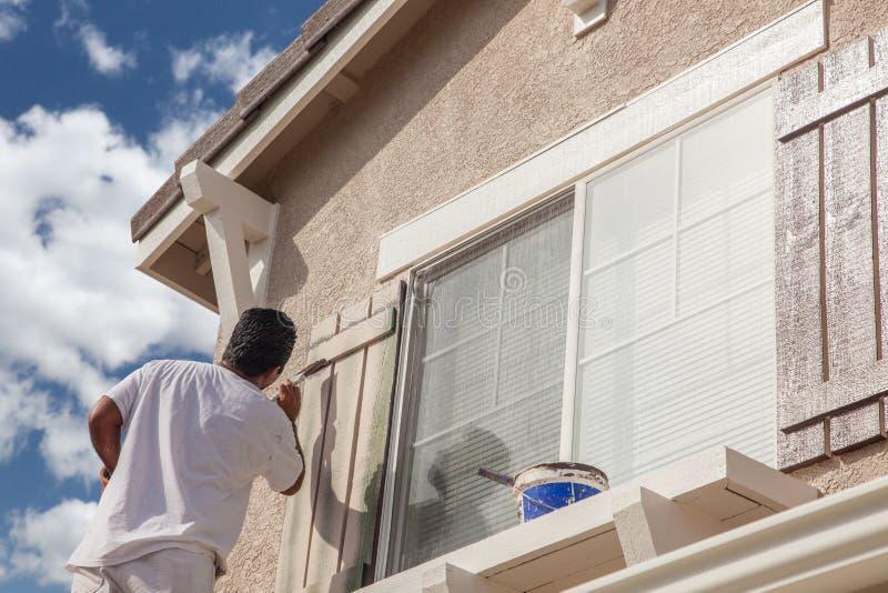 Επαγγελματικός ζωγράφος σπιτιών που χρωματίζει την περιποίηση και τα παραθυρόφυλλα του Α Χ στοκ φωτογραφίες με δικαίωμα ελεύθερης χρήσης