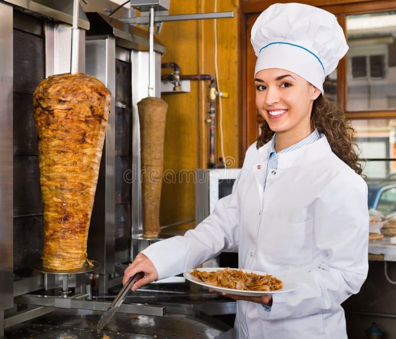 Επαγγελματικός θηλυκός μάγειρας με το ψημένο στη σχάρα κρέας στον οβελό για το kebab στοκ φωτογραφίες