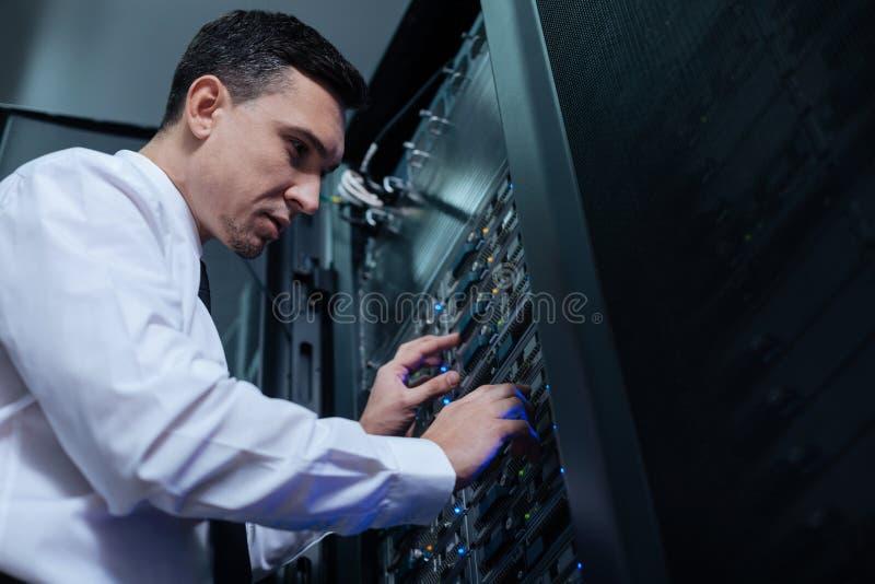 Επαγγελματικός μηχανικός υπολογιστών που εξετάζει τον κεντρικό υπολογιστή στοιχείων στοκ φωτογραφίες με δικαίωμα ελεύθερης χρήσης