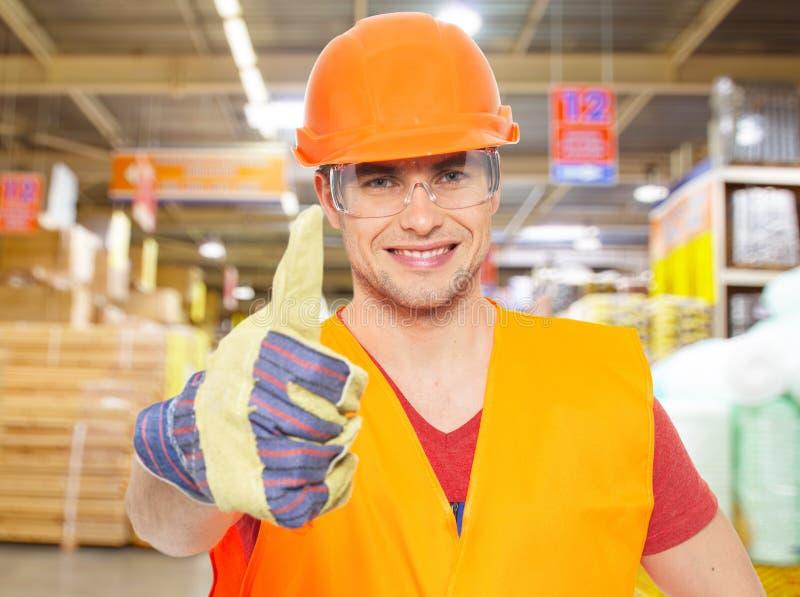 Επαγγελματικός νέος εργαζόμενος με τους αντίχειρες επάνω στο κατάστημα στοκ φωτογραφία με δικαίωμα ελεύθερης χρήσης