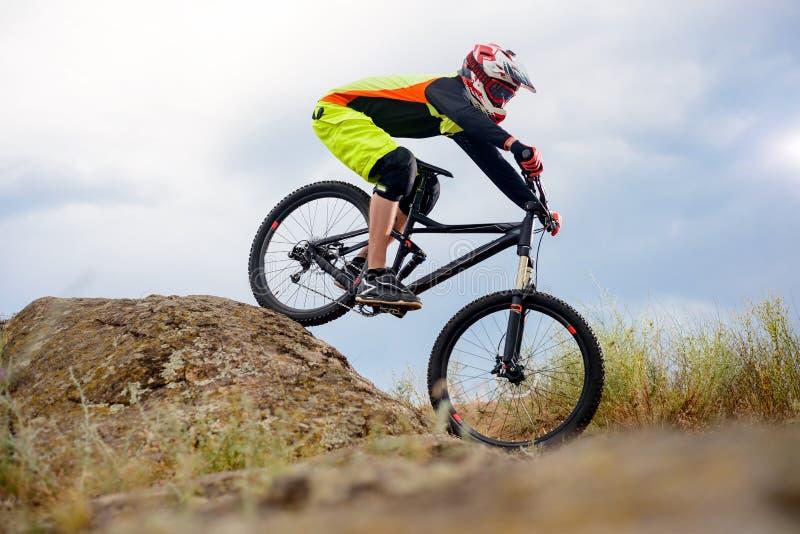 Επαγγελματικός ποδηλάτης που οδηγά το ποδήλατο κάτω από το δύσκολο Hill Ακραία αθλητική έννοια Διάστημα για το κείμενο στοκ εικόνες με δικαίωμα ελεύθερης χρήσης